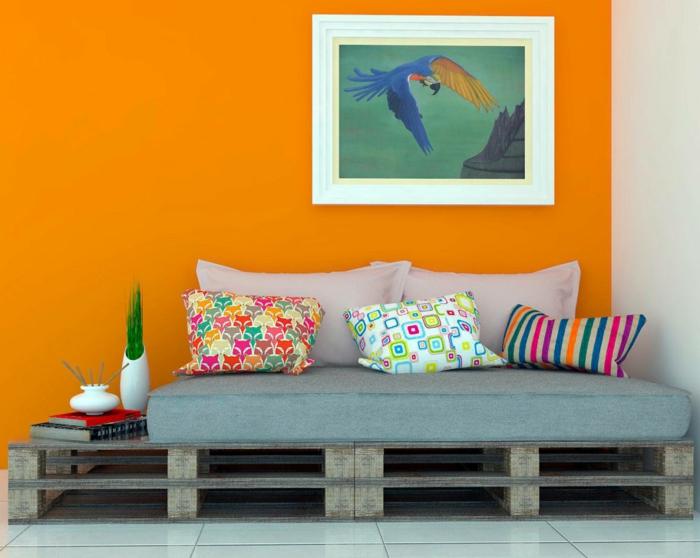 decoracion de interiores en colores llamativos, sillones con palets con colchonetas y cojines coloridos, pared en color naranja y pintura