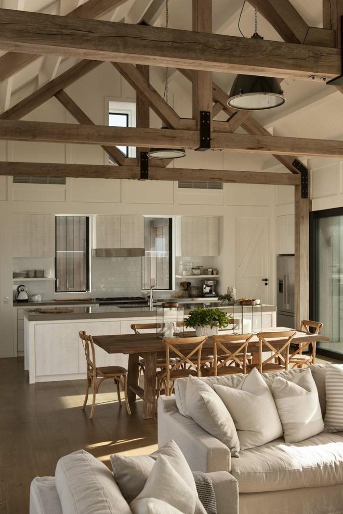 buhardilla de encanto decorada en blanco con vigas de madera, muebles cómodos modernos en beige, ideas cómo decorar un salón comedor