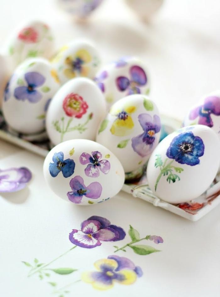 como decorar huevos de pascua con motivos florales, huevos con bonita decoración, dibujos de violetas en diferentes colores