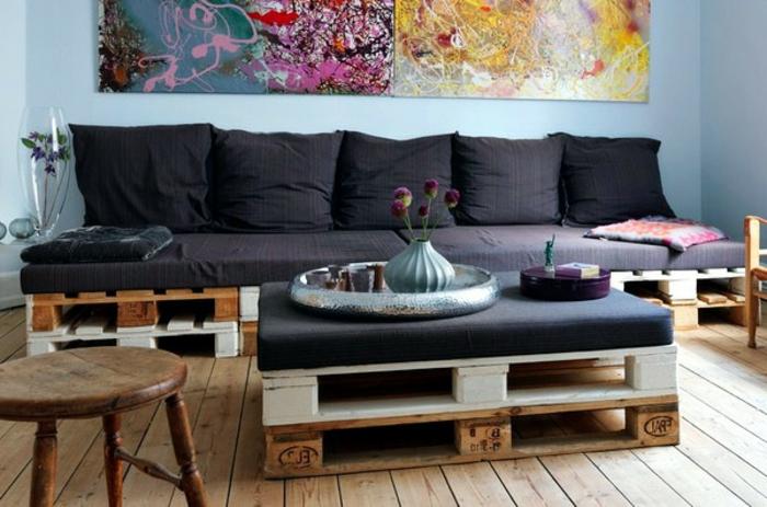 salón moderno decorado de sofa palets y mesa de pareds con colchonetas negras, suelo de madera y pared en azul