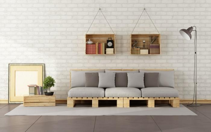 salon decorado en estilo industrial moderno, pared de ladrillo y sofa palets en gris, suelo con baldosas