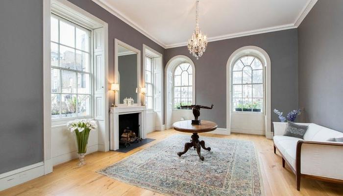 espacio de diseño minimalista en estilo vintage, muebles de época, candelabro vintage y paredes en gris plomo, salón gris y blanco ideas