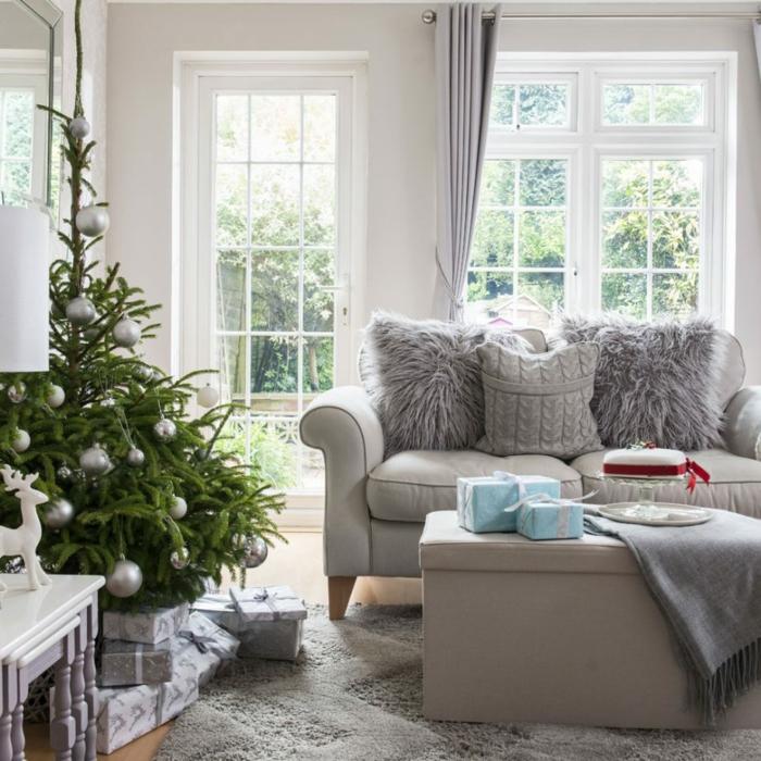bonita decoracion de salones en gris, sofá y mesa en gris, decoración navideña, grandes ventanales blancos con cortinas en gris