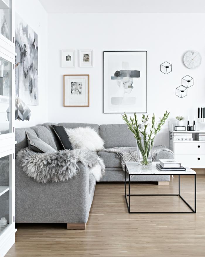 decoracion de salones en estilo nórdico, sofá en gris plata con cojines decorativos en blanco y negro, paredes en blanco con cuadros decorativos