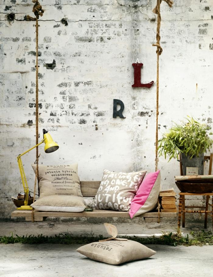 sofa palets y bancos de palets para decorar el jardín, decoración en estilo vintage, pared de ladrillo efecto envejecido y lampara en amarillo
