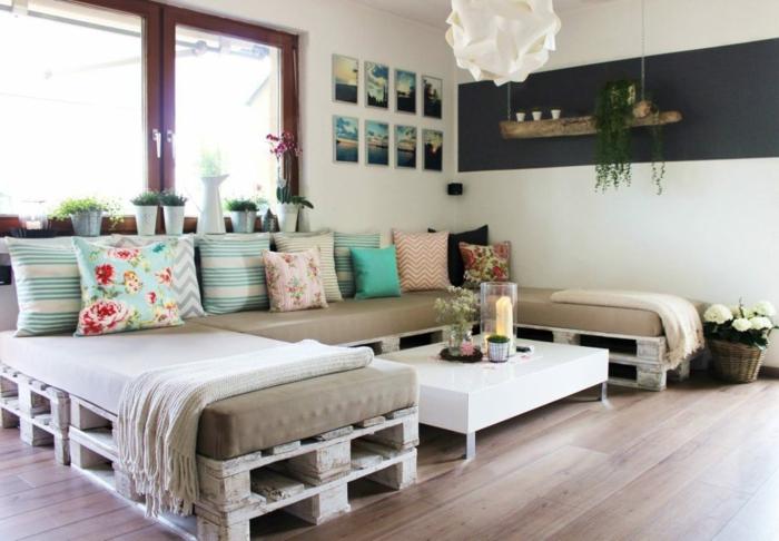 precioso salón con grande sofá de palets, muebles de palets para decorar el hogar, muchos cojines decorativos con estampados de flores