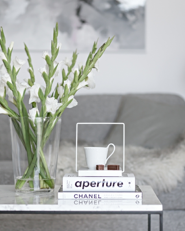 ideas de decoracion de salones, pequeña mesa moderna, jarrón de vidrio con flores y libros, diseño minimalista en blanco y gris