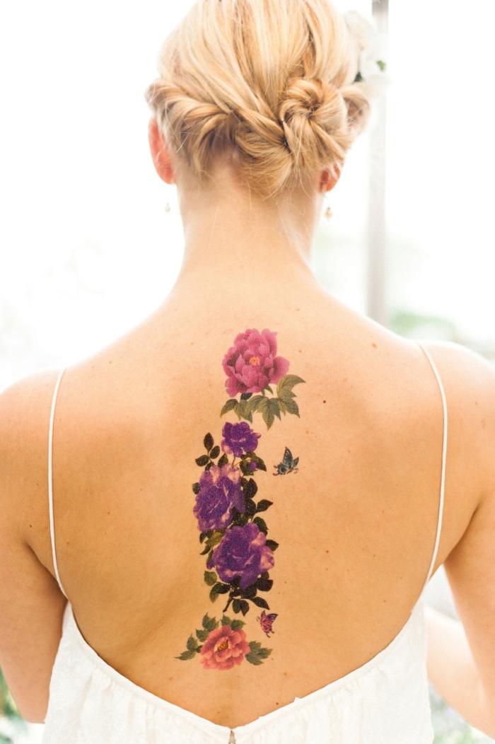 preciosas ideas de tatuajes para mujeres con flores, bonita cadena de flores en la columna vertebral, flores en rosado y lila