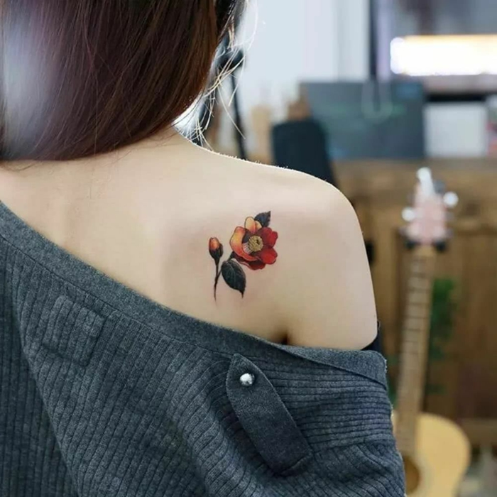 ejemplos de tatoos pequeños en la espalda, detalle bonito tatuado en la espalda, tatuaje de flor en rojo y amarillo