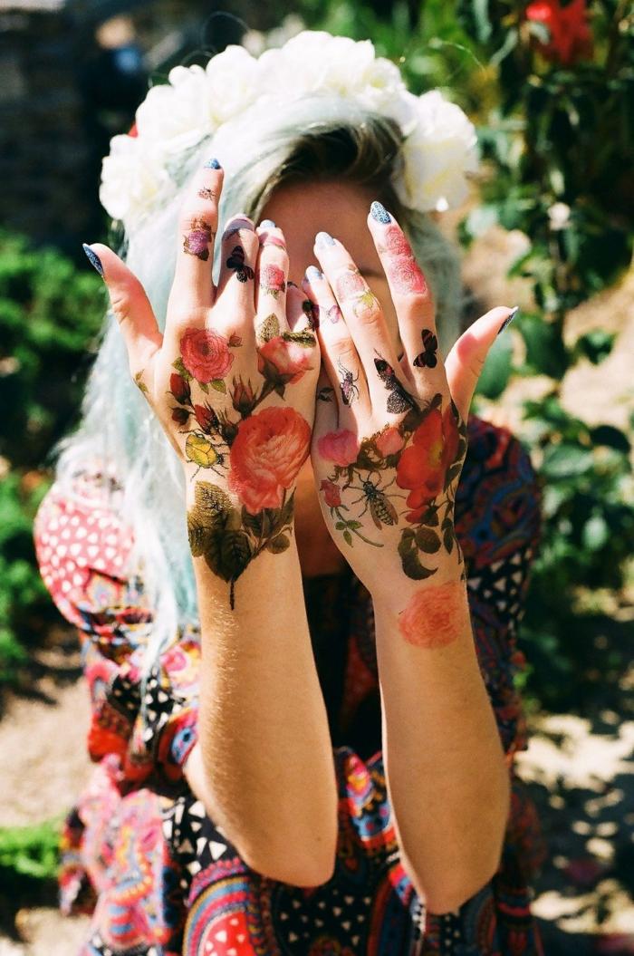 mujer con las manos y dedos tatuados, tatuajes con motivos florales y dibujos de insectos, tatoos pequeños en los dedos