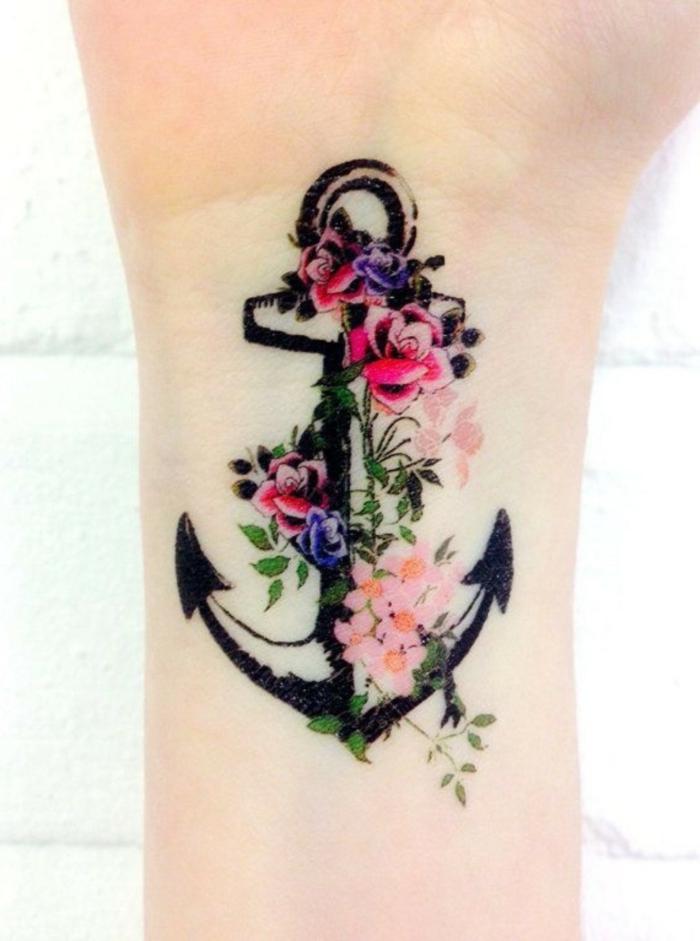 precioso detalle tatuado en el antebrazo cerca de la muñeca, ancla con flores, ejemplos de tatoos pequeños con motivos florales