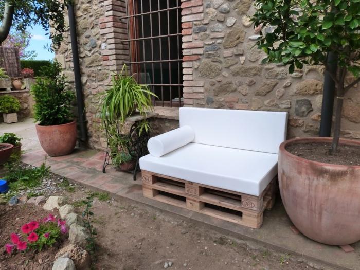 como decorar el jardin con muebles de palets, banco hecho de palets con colchonetas en blanco, grandes macetas con plantas verdes