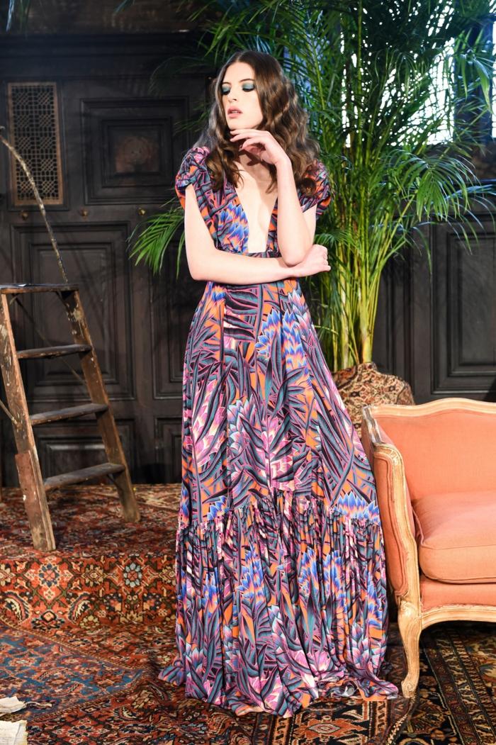 modelo de encanto, largo vestido en colores cálidos con estampado de flores y grande escote, tendencias vestidos hippies