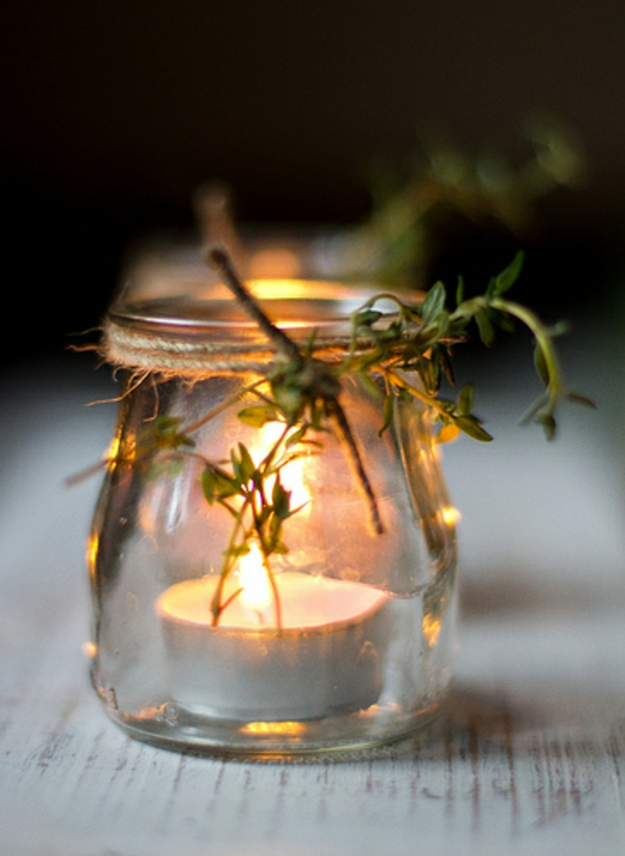 ejemplos de botes decorados de una manera original, pequeño frasco de vidrio con una vela dentro y decoración de plantas verdes