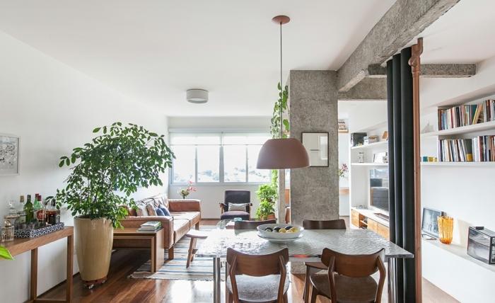 grande salon con comedor, decoración de plantas verdes e interesantes elementos arquitectónicos, cortinas como separador de ambientes