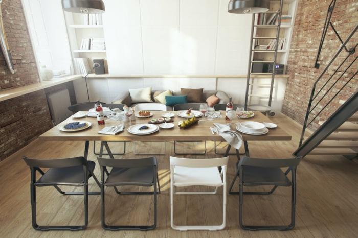 precioso salon abierto al comedor, sillas de diseño igual y diferente color, paredes de ladrillo y suelo de parquet