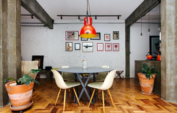 ambiente acogedor con detalles en colores llamativos, salon comedor con paredes de ladrillo y grandes maceteros con plantas verdes