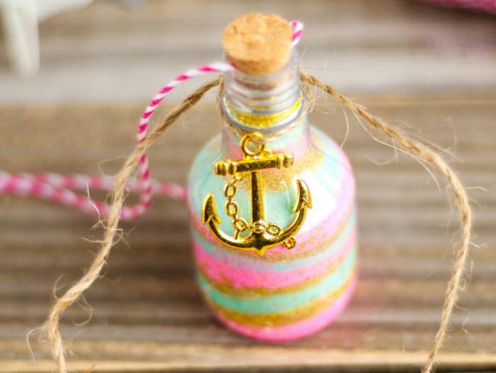 ideas encantadoras de manualidades con botellas de cristal, botellas de vidrio colorida decorada con purpurina y elemento dorado colgante