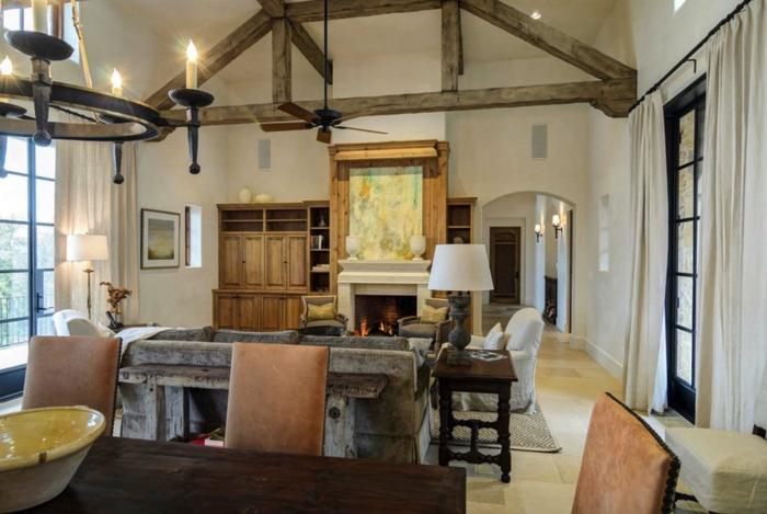 salon abuhardillado con decoración de encanto, techo con vigas de madera y muebles rústicos