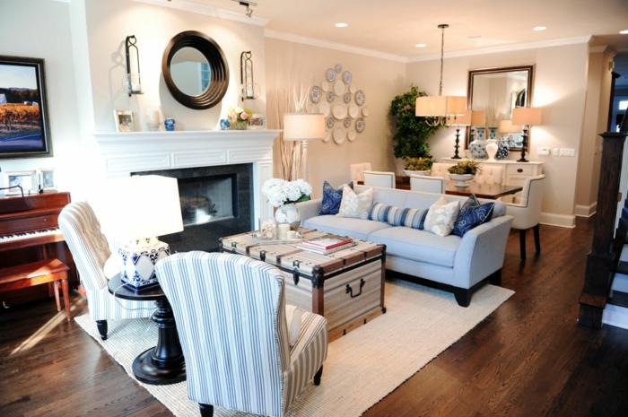 espacio decorado en estilo vintage, salon con sillones y sofa en azul celeste y blanco, suelo de parquet y y mesa de diseño original