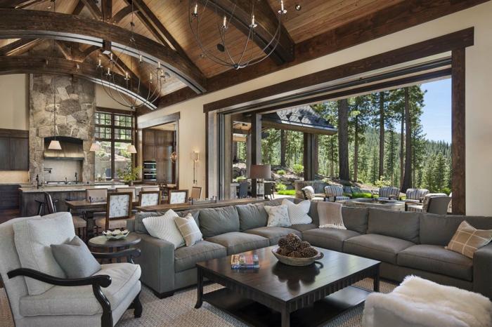 grande salon en estilo rustico con ventanales y techo de madera, habitación abuhardillada, sofá en esquina en gris