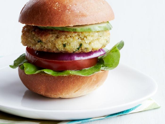 como se prepara la quinoa para hacer una hamburguesa rica, panecillo pequeño con pepinos, cebolla, tomate, lechuga y hamburguesa de quinoa