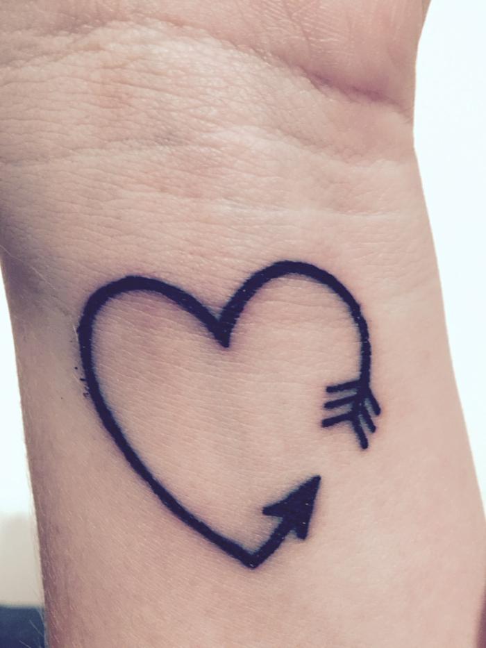 bonitas ideas de tatuajes para mujeres en el brazo, tatuaje en forma de corazón con flecha con tinte negro