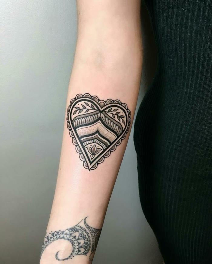 ideas de tatuajes para mujeres en el brazo, tatuaje llamativo con tinte negro en forma de corazón ornamentado con elementos florales