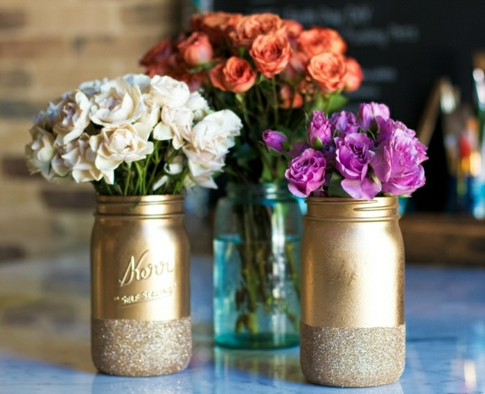 bonitas ideas sobre como decorar botes de cristal, botes pintados en dorado con decoración de purpurina, preciosos jarrones de flores DIY