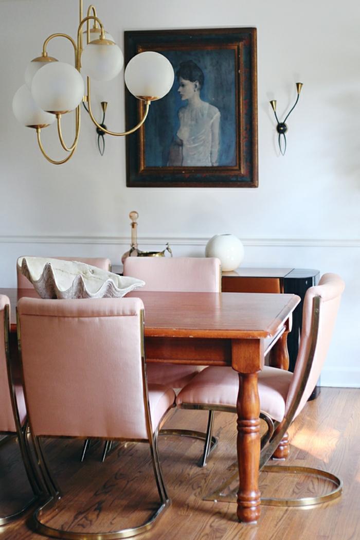ejemplos de decoracion salones y comedores en estilo vintage, bonita pintura en la pared, mesa de madera y sillas originales color rosa