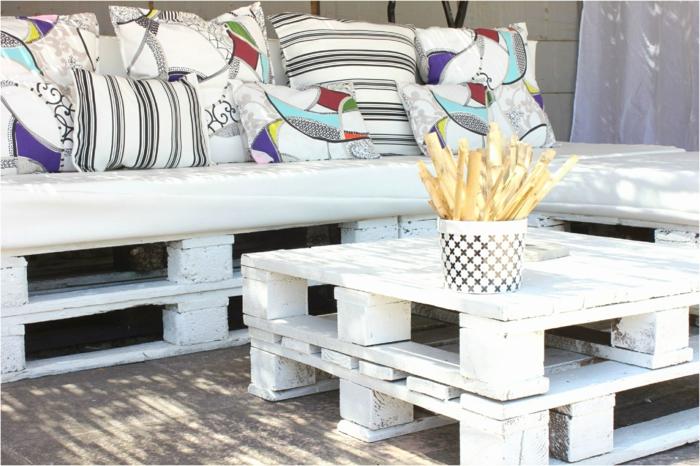 preciosas ideas de decoracion con palets, palets de madera pintados en blanco y muchos cojines decorativos en colores