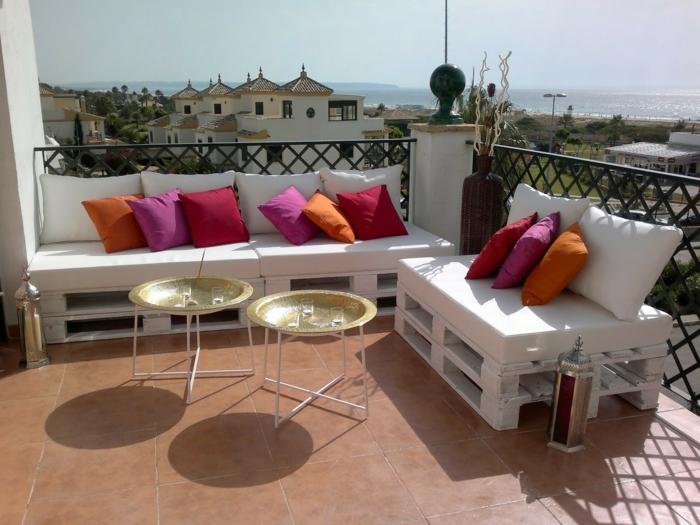 terraza moderna con bonita vista al mar, decoracion con palets y cojines decorativos en rojo, rosado y naranja