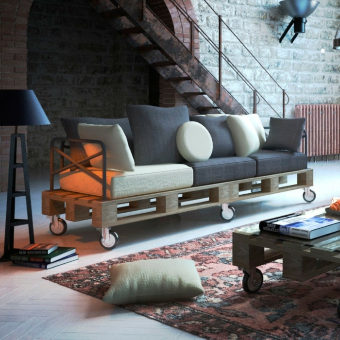 salón en estilo industrial con muebles hechos con palets, sofá en ruedas DIY y escaleras de hierro