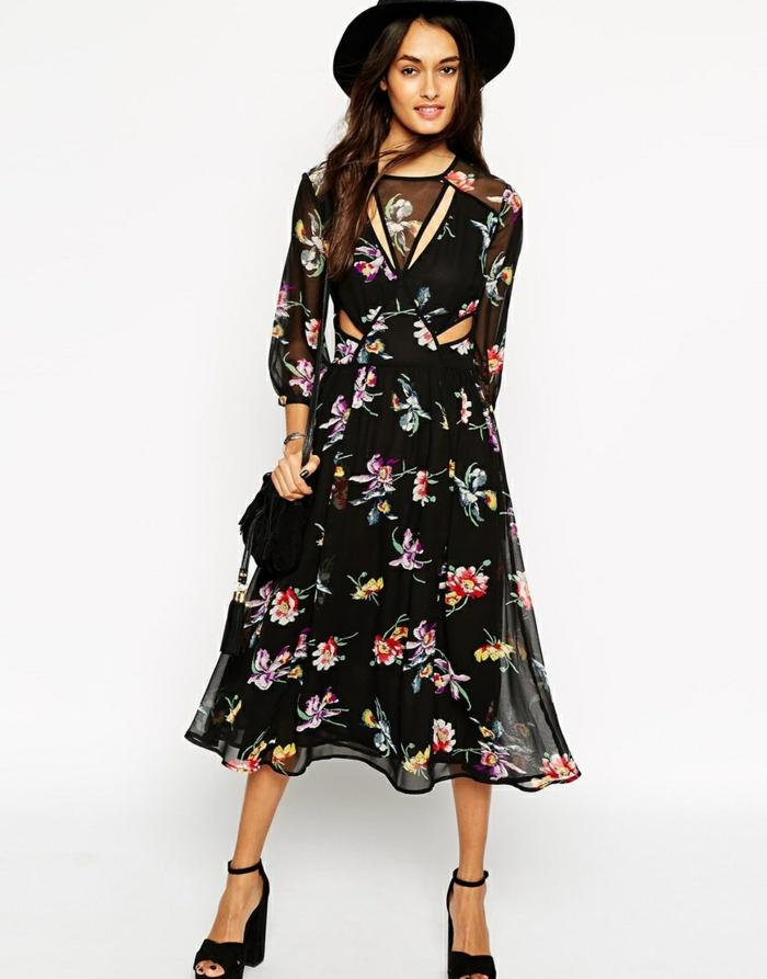 fantásticas propuestas de vestidos largos hippies, vestido en negro con estampados de flores coloridos, zapatos abiertos en tacón alto y sombrero negro