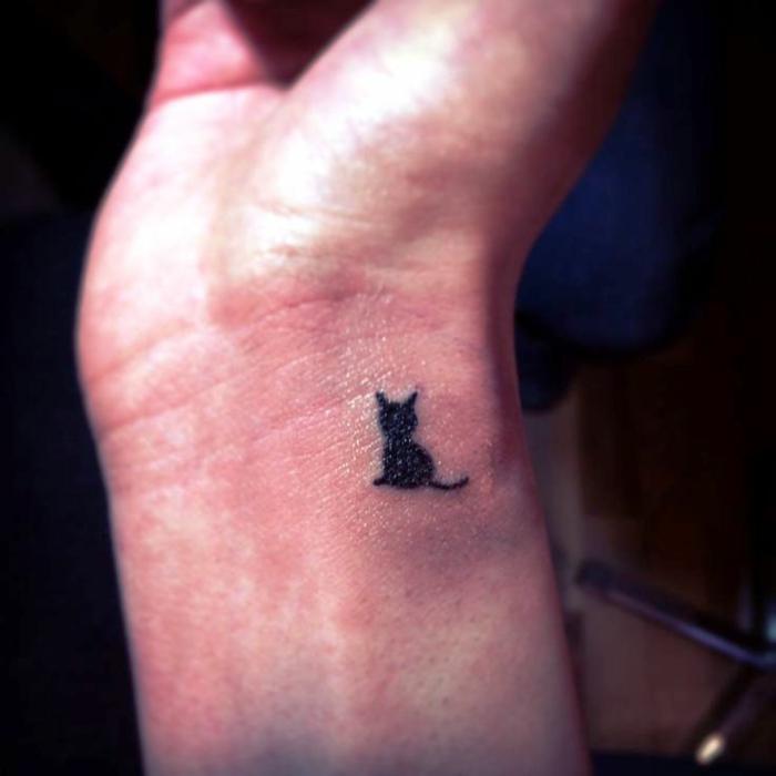tatuaje pequeño de encanto en forma de un gato, pequeño detalle dibujado en la muñeca en negro, ideas tatuajes de mujer