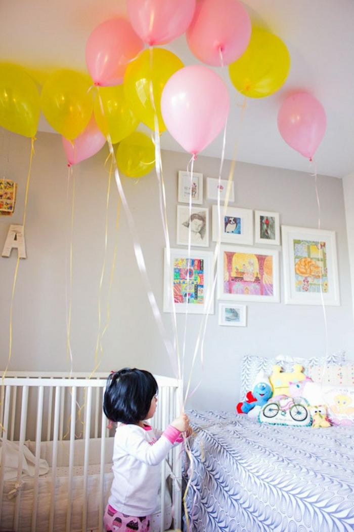 decoracion fiesta cumpleaños con globos en amarillo y rosado, dormitorio infantil decorado de manera encantadora