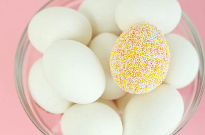 huevos blanco decorados con bolas de azúcar en colores pastel, huevo en amarillo verde y rojo