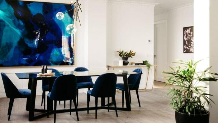 comedor elegante con muebles de diseño, grande pintura en la pared como punto focal y decoración de flores, decoracion salon pequeño ideas prácticas