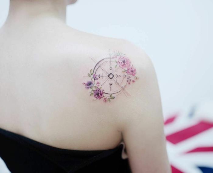preciosa brújula decorada de flores en rosado y lila, ejemplos espectaculares de tatuajes espalda mujer