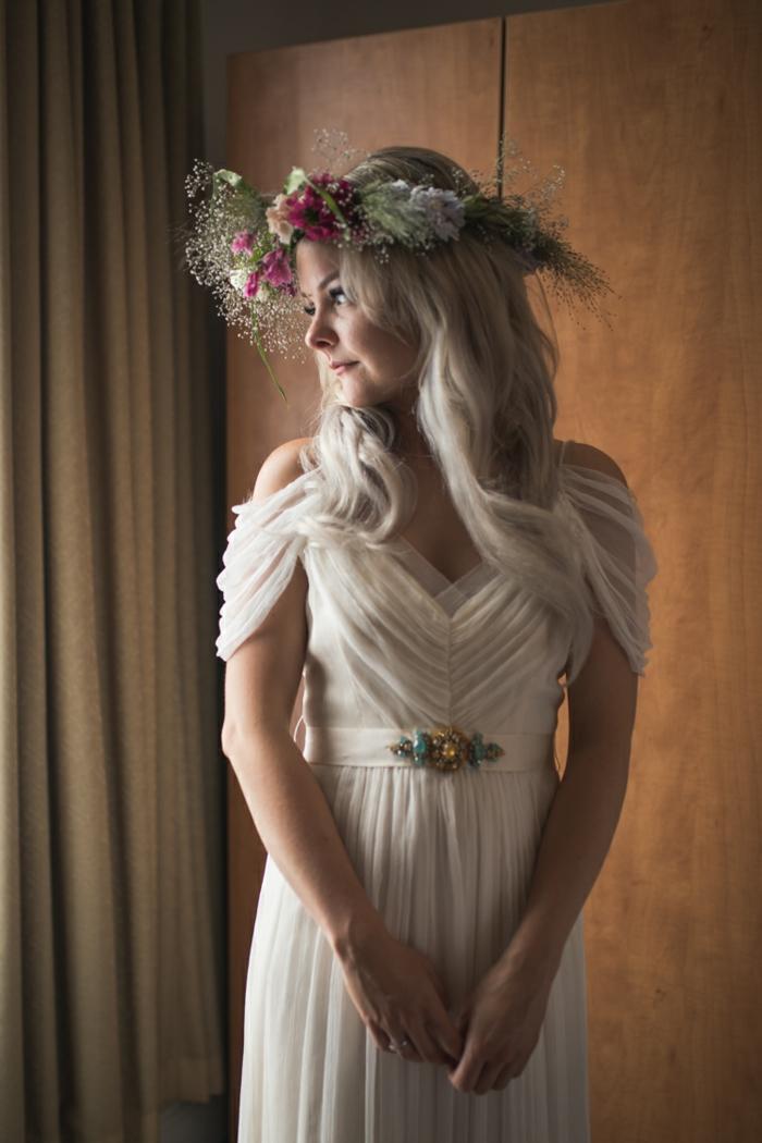 vestido de novia de tul con mangas sueltas en color marfil, pelo suelto ondulado y tiara de flores coloridos