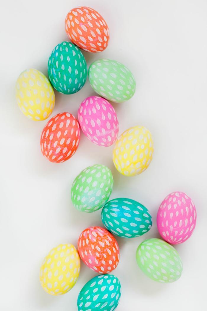 bonita decoración con huevos de pascua, huevos pintados en verde, naranja, rosado y amarillo con dibujos en blanco