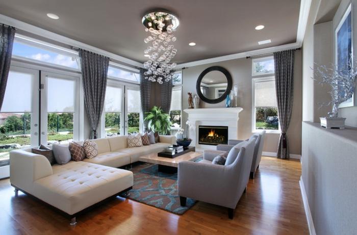 paredes grises y techo en el mismo color, grande salón con sofá color champán en capitoné y lampara de diseño original