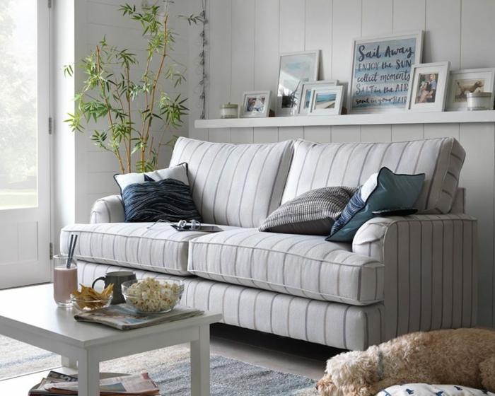 pequeño rincón de un salón decorado en blanco y gris, sofá tapizada en rayas, muchos cuadros decorativos y decoración de plantas verdes
