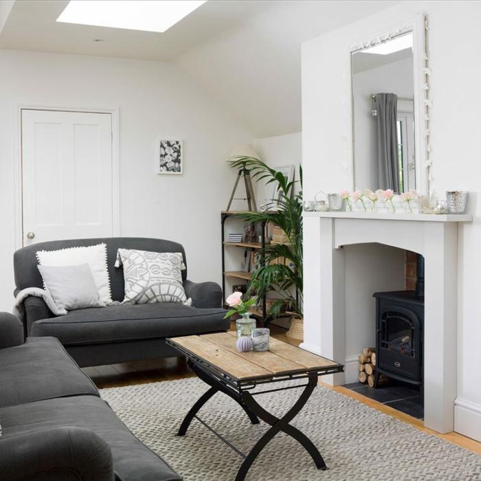 ideas para decorar un salon en blanco y gris, diseño sencillo con decoración de plantas verdes y chimenea de leña
