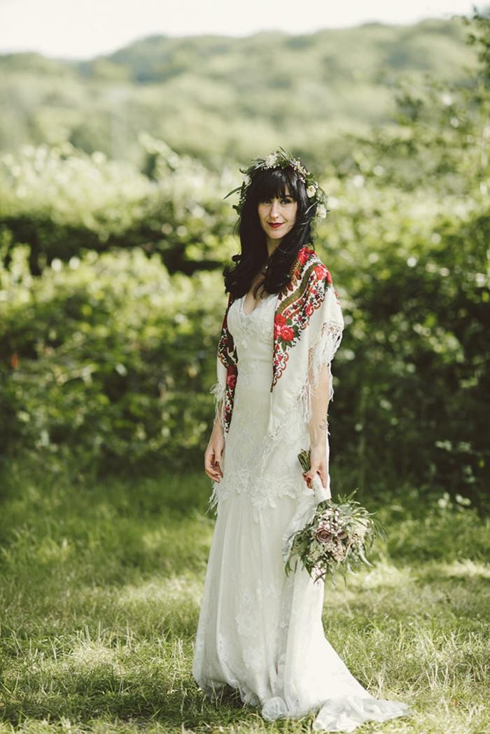 ejemplo encantador de vestidos hippies, largo vestido color champán con bufanda colorida, ramo de flores y corona de flores en el pelo