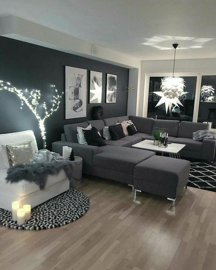 salon decorado en estilo clásico con muchas lámparas y paredes grises, grandes sofá en gris oscuro y suelo de parquet