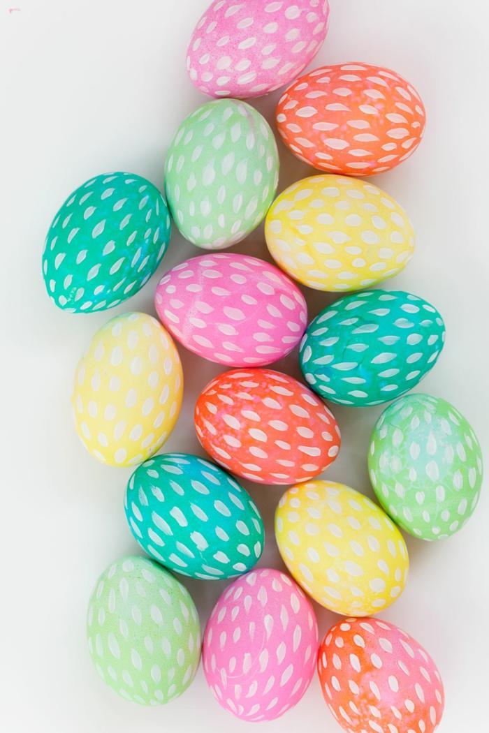 huevos de pascua decorados en colores claros y llamativos, huevos coloreados con decoración de rayas