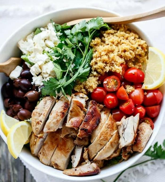ensalada con muchos nutrientes de pollo, aceitunas, tomates cherry, quinoa blanca, perejil y limones, ideas comidas rapidas y faciles
