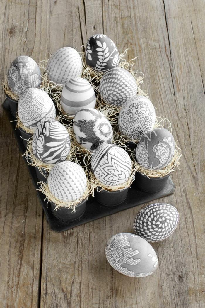 decoración sofisticada en gris, huevos de pascua para colorear blancos con bonitos dibujos con motivos florales y geométricos