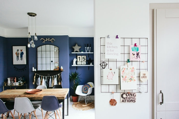 decoracion comedor en tonos oscuros, paredes en azul con muchos detalles decorativos, mesa con toque vintage y sillas en diferentes colores